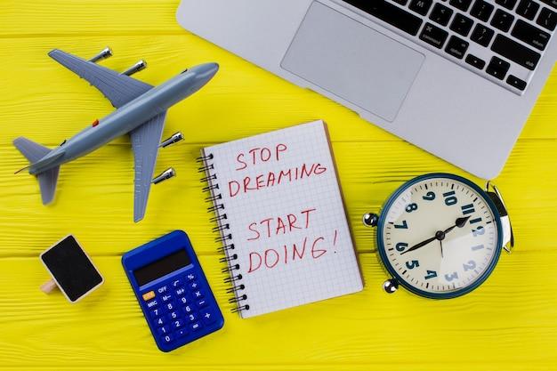 Плоская планировка путешествий и финансов. перестань мечтать, начни делать. самолет, калькулятор, будильник и ноутбук.