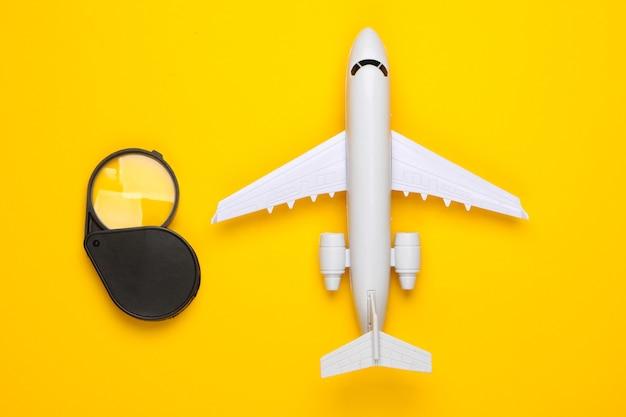Плоская планировка путешествия. фигурка самолета и лупа на желтом.