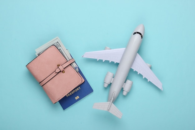 Flat lay travel composition on a blue. plane figurine, passport, wallet with dollars