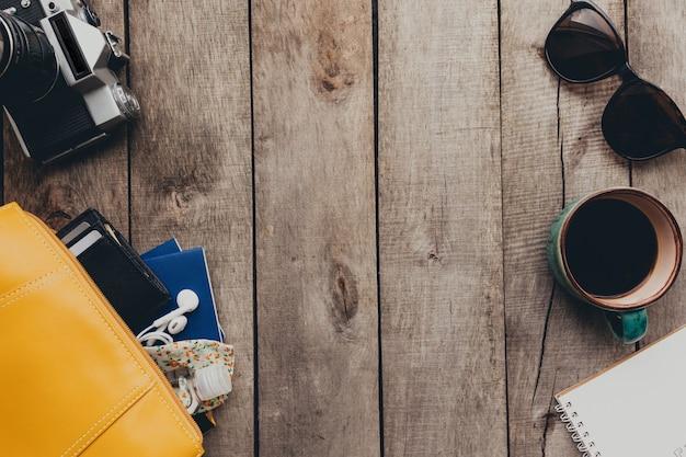 パスポート、黒い財布、ハンドバッグ、保護マスクと消毒剤、メモ帳とイヤホン、眼鏡、コーヒー、木製の背景に写真カメラを備えたフラットレイ旅行のコンセプト。