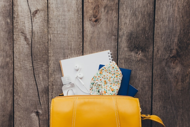 ハンドバッグにパスポート、保護フェイスマスクと消毒剤、メモ帳、木製の背景にイヤホンを備えたフラットレイトラベルコンセプト。