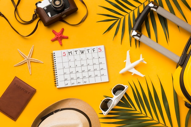 Flat lay of travel essentials with calendar and sunglasses