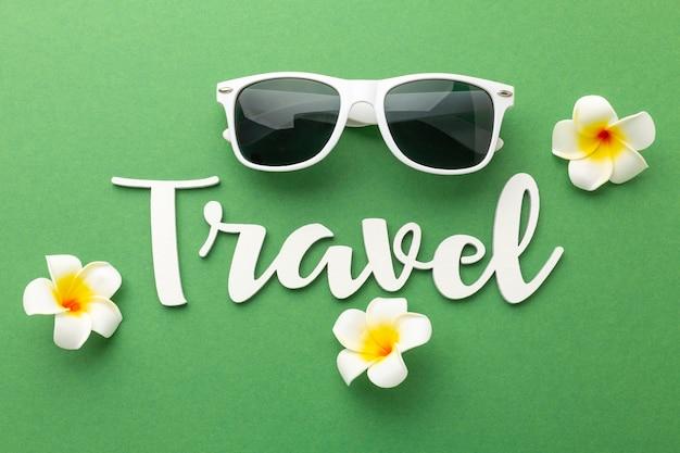 緑の背景にフラットレイ旅行アイテム