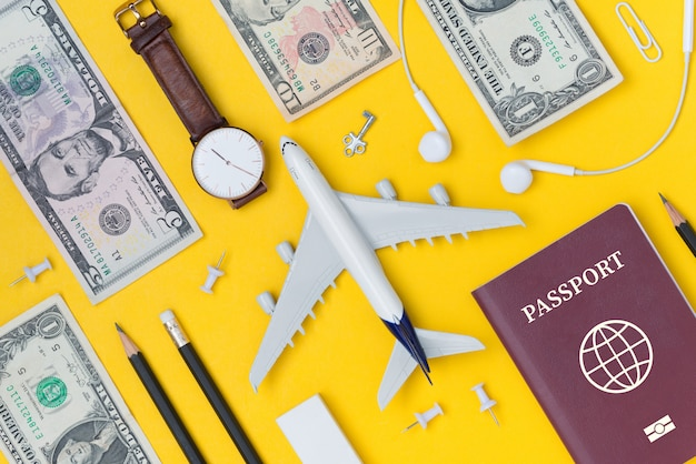 Flat lay of travel planning with airplane, pencil, watch, money, paper note, earphone and passport