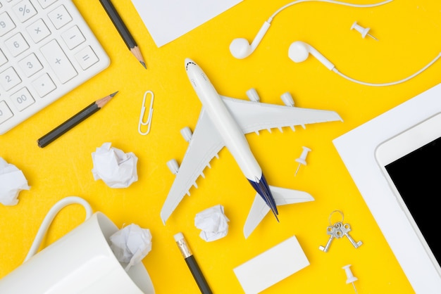 Flat lay of travel planning with blank space on yellow background