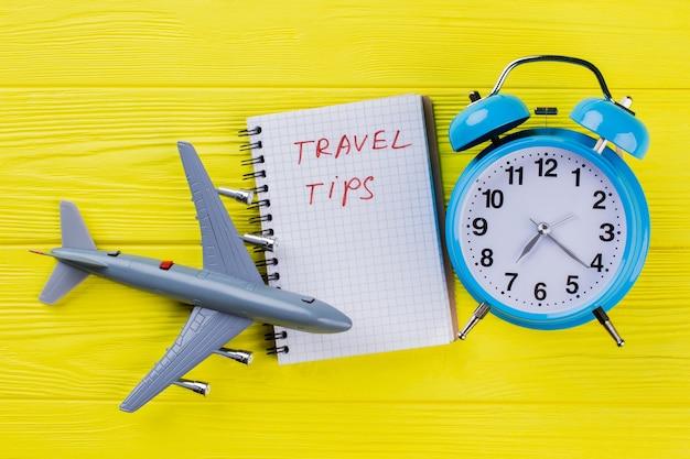 フラットレイ旅行のヒントの概念。黄色い木の上のメモ帳と目覚まし時計付きのプラスチック飛行機。