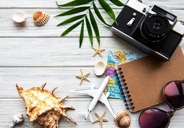 テキストの空白スペースを持つ木製の背景にフラットレイアウトの旅行者のアクセサリー。トップビューの旅行や休暇の概念。夏の背景。