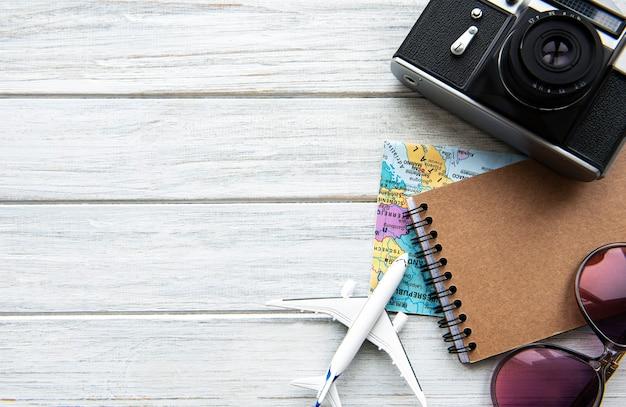 テキスト用の空白のある木製の背景にフラットレイトラベラーアクセサリー。トップビューの旅行や休暇の概念。夏の背景。