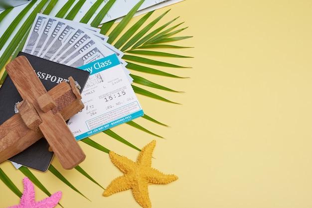 팜 리프, 카메라, 신발, 모자, 여권, 돈, 항공권, 비행기 및 선글라스와 노란색 배경에 평평하다 여행자 액세서리. 상위 뷰, 여행 또는 휴가 개념. 여름 배경.