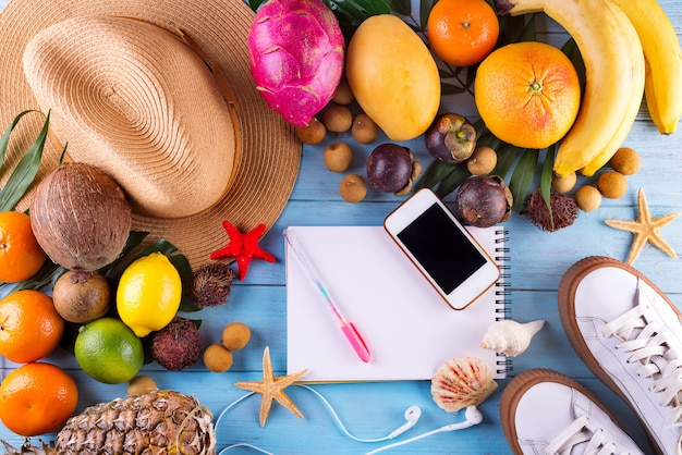 Flat lay traveler accessories and tropical fruits on wooden background