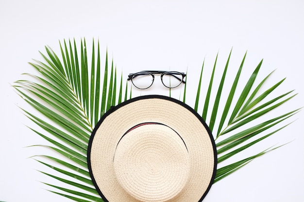 Flat lay traveler accessories on white background with palm leaf and hat. summer concept.