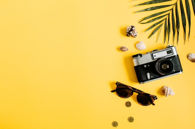 Flat lay traveler accessories on yellow with palm leaf, camera and sunglasses