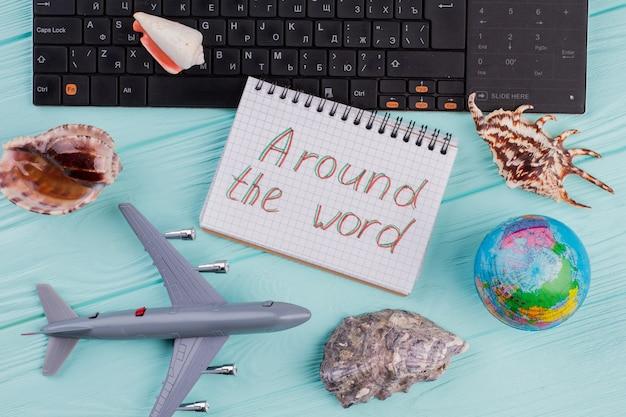 파란색 책상 위에 비행기, 지구, 조개, 메모장이 있는 평평한 여행 구성. 노트북에 쓰여진 전세계.