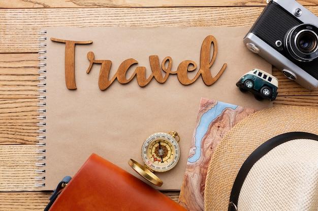 木製の背景にフラットレイ旅行アイテム