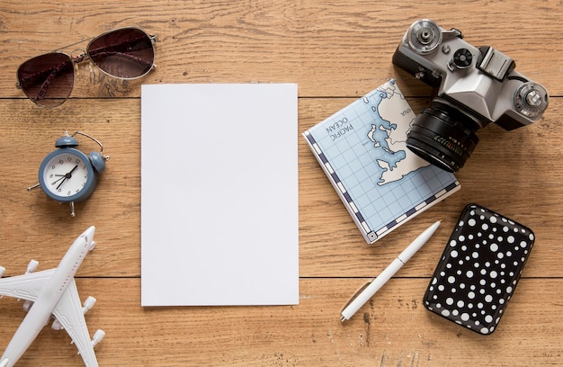 Flat lay traveling items on wooden background
