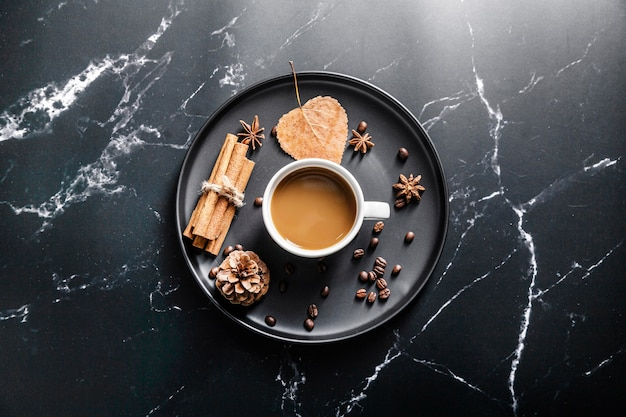 Flat lay of tray with coffee cup and cinnamon sticks