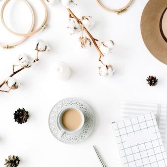 コーヒー、コットンブランチ、日記を使った、トレンディでクリエイティブなフェミニンなアクセサリーのアレンジメント。帽子、綿の枝、ノートブック、コーヒーカップ、モミの円錐形、白の金色のクリップ
