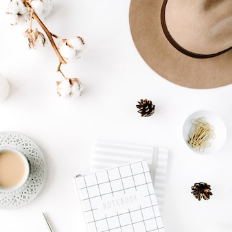 Flat lay trendy creative feminine accessories arrangement with coffee, cotton branch and diary. hat, cotton branch, notebook, coffee cup, fir cone, golden clips on white background.