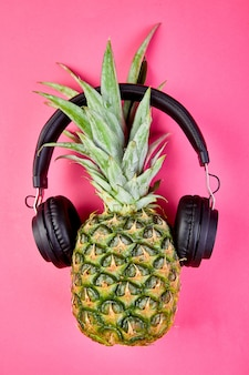 Flat lay of trendy, funny face pineapple fruit with headphones.