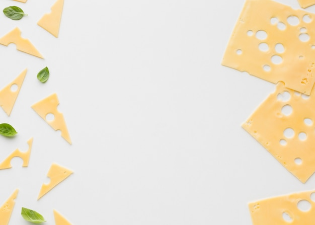 Flat lay triangular and square emmental cheese slices with copy spaces