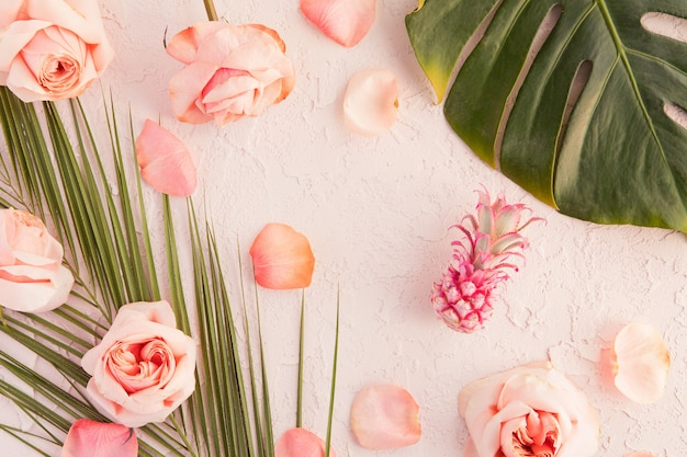 Flat lay of tropical workspace mockup with palm monstera leaves, pink flowers, pineapple and petals on pastel