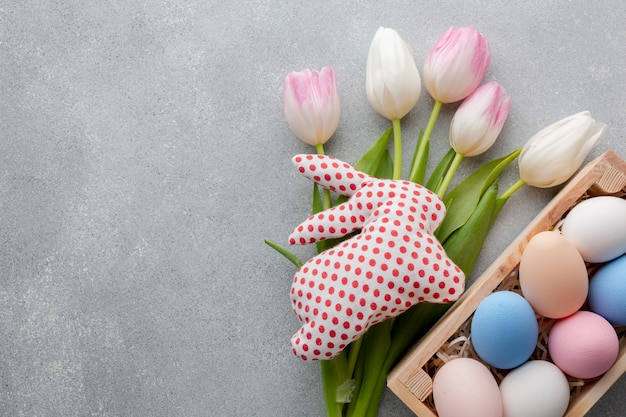 Flat lay of tulips and colorful easter eggs in box