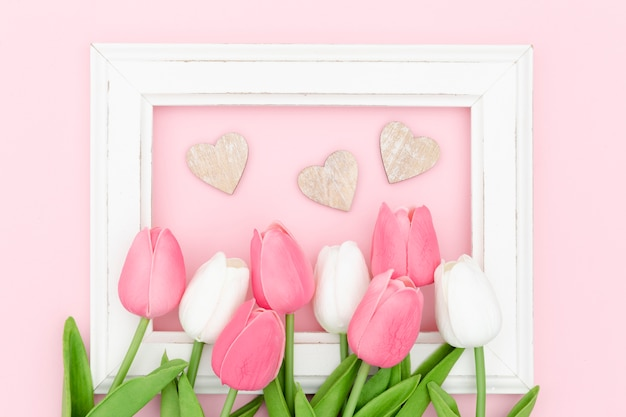 Flat lay of tulips with frame and hearts