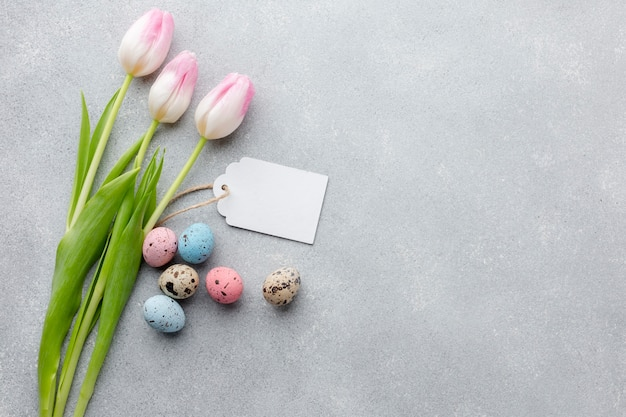 Flat lay of tulips with tag and colorful easter eggs
