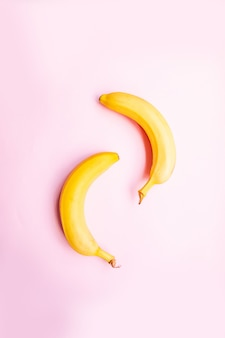 Flat lay  two bananas on pink background.