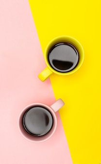 Flat lay of a two coffee cups with pink and yellow