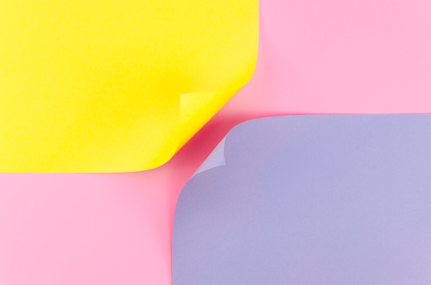 Flat lay of two colorful paper sheets with bent corners