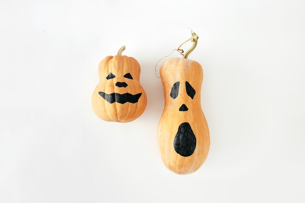 Flat lay two funny scary face halloween pumpkins white  top view