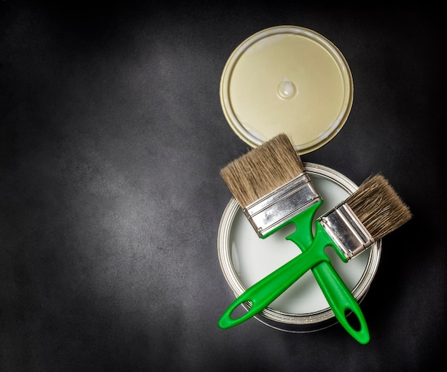 Flat lay, two green brushes and an iron can of paint, on a black textured background.