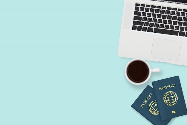 Flat lay of two passport , coffee cup and computer laptop on pastel blue color with copyspace