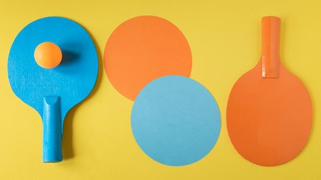 Lay piatto di due racchette da ping pong con palla