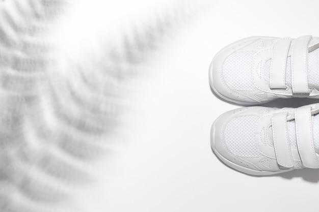 Две белые детские кроссовки унисекс на липучке с тенями папоротника или пальмы.