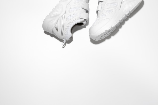 Flat lay two white unisex sneakers on the side at the top with free space for text isolated on a whi...