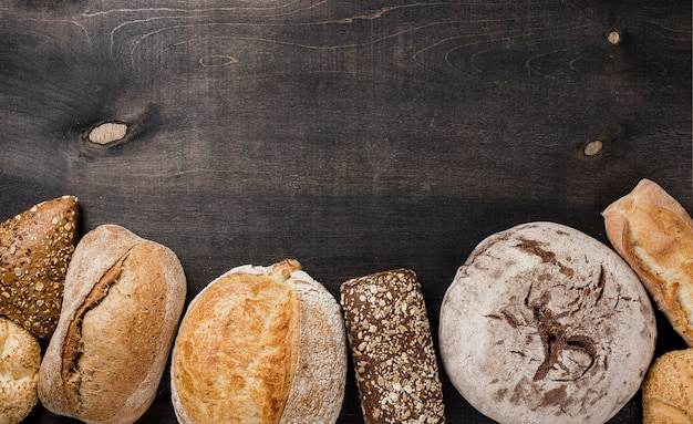 Flat lay types of bread and black copy space background