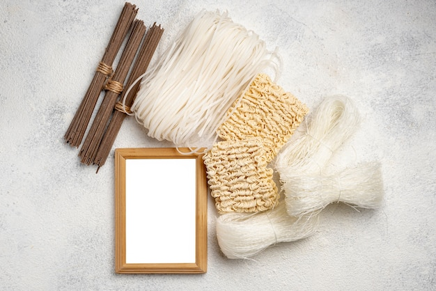 Flat lay uncooked assortment of noodles with blank frame