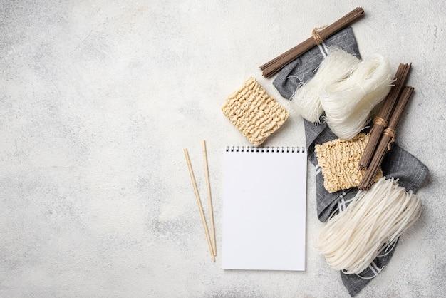 Assortimento crudo di noodles piatti laici con taccuino vuoto e copia spazio