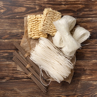 Flat lay uncooked assortment of noodles on wooden background