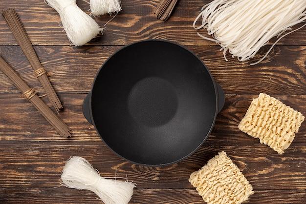 Плоский лежал сырой ассортимент лапши на деревянном фоне с тарелкой