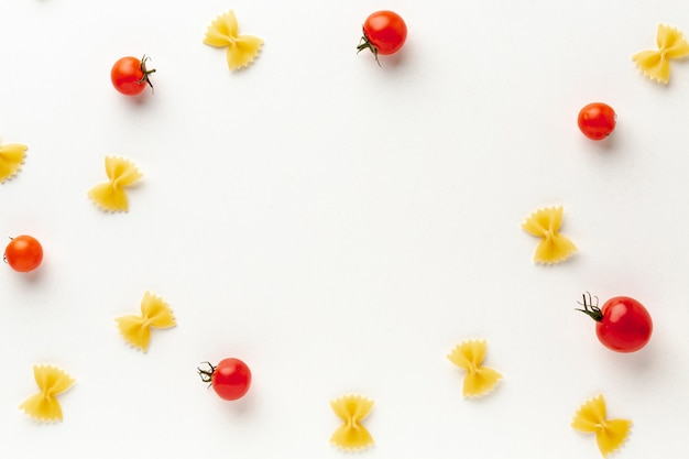 Flat lay uncooked farfalle arrangement with tomatoes with copy space