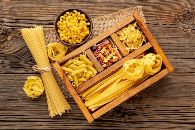Flat lay uncooked pasta mix in wooden box