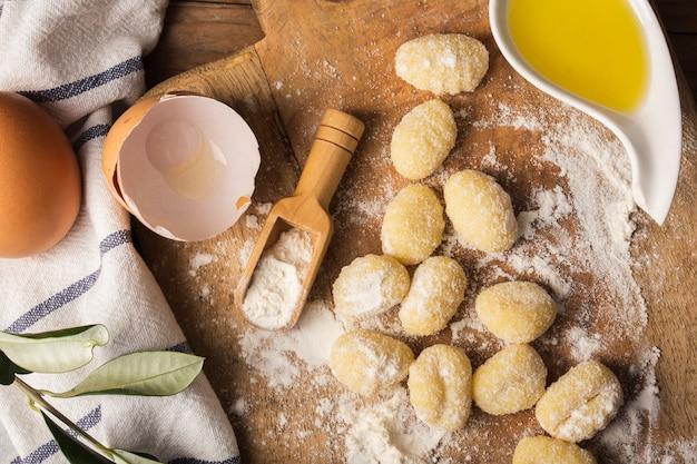 Flat lay uncooked potato gnocchi on cutting board