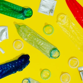 노란색 배경에 평평하다 래핑되지 않은 콘돔