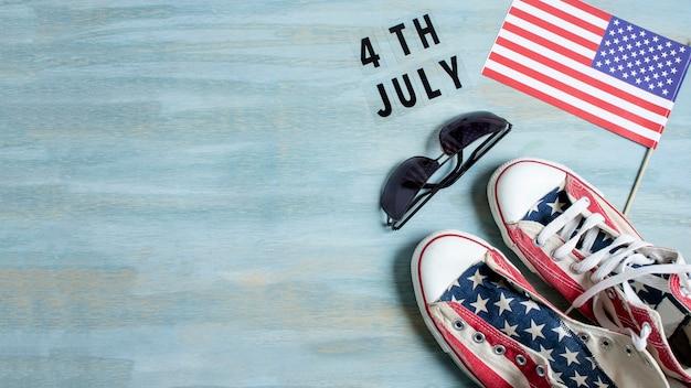 フラット横たわっていたアメリカの国旗のスニーカーとコピースペース付きサングラス