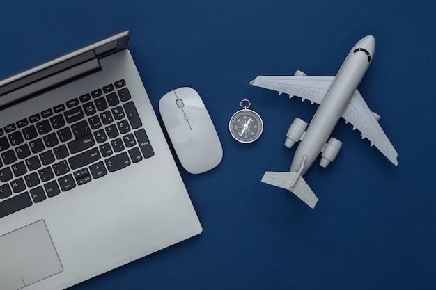 フラットレイ休暇休暇と旅行プレーニングの概念。古典的な青い背景のラップトップと旅行アクセサリー。上面図