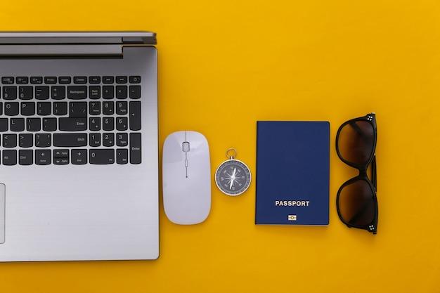 평평한 휴가 휴가 및 여행 계획 개념. 노란색 배경에 노트북 및 여행 액세서리입니다. 평면도