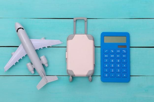 평평한 휴가 휴가 및 여행 계획 개념. 파란색 나무 배경에 미니 플라스틱 여행 가방, 비행기, 계산기. 평면도